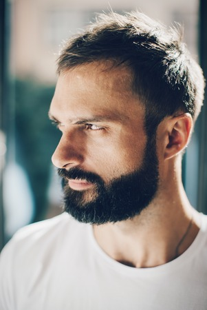man looking out: Portrait of a bearded man looking out the window wearing white tshirt