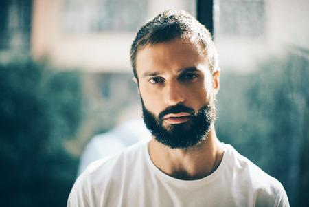 hombre pensando: Retrato de un hombre con barba y guapo wering camiseta blanca y pensando en algo