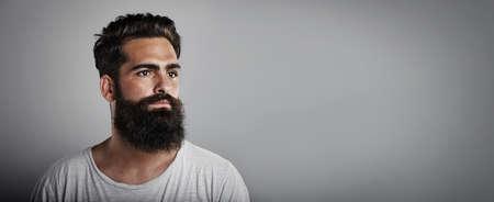hombres jovenes: Claro de larga barba y bigote hombre vistiendo la camiseta blanca en el fondo gris