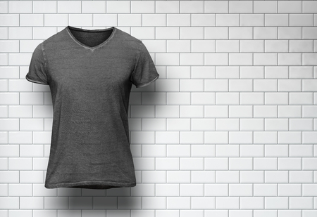 gray clothing: Dark tshirt isolated on the white bricks wall