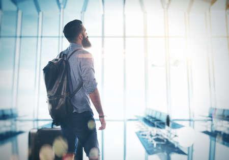 in  shirt: Hombre barbudo de pie en el aeropuerto con una maleta y la mochila Foto de archivo