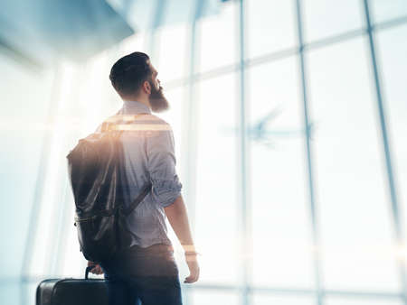 airport: Bearded man standing at the airport with a suitcase and backpack Stock Photo