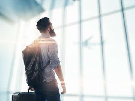 maletas de viaje: Hombre barbudo de pie en el aeropuerto con una maleta y la mochila Foto de archivo