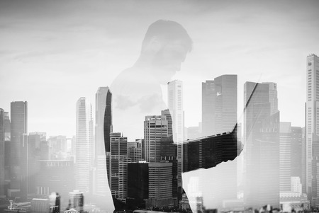 multiple exposure: Double exposure of young man using laptop and panoramic city view on the background Stock Photo