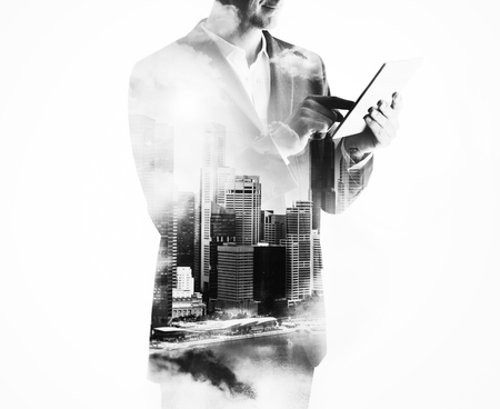 black professional: Tablet holding in businessman hands. Double exposure of panoramic city view on the background Stock Photo