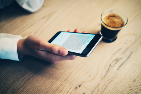 hand phone: Smartphone holding infemale hand and drinking cup of espresso. Reading a text on the screen