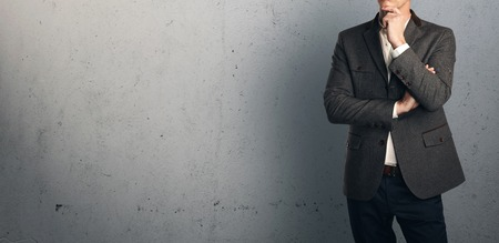 businessman suit: Young businessman standing and thinking on the background of a concrete wall Stock Photo