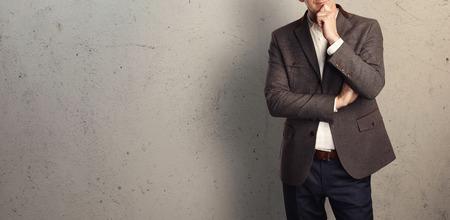 traje: Joven empresario de pie y pensar en el fondo de un muro de hormigón Foto de archivo