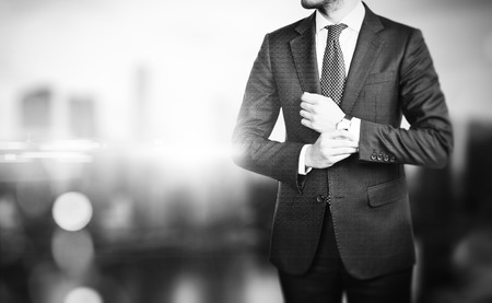 Black and white picture of young  businessman touching his watch and the city on the blured background