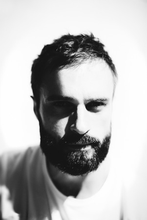 textil: Black and white portrait of a handsome bearded man wearing white tshirt and sunlights on his face