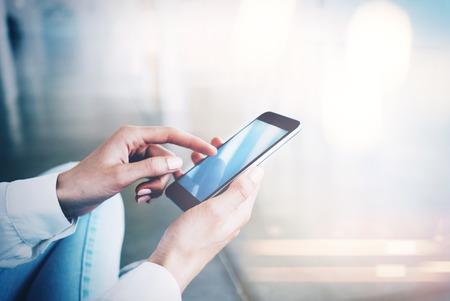 젊은 여성이 바닥에 앉아 손에 그녀의 스마트 폰을 들고와 그 위에 화면을 누르면