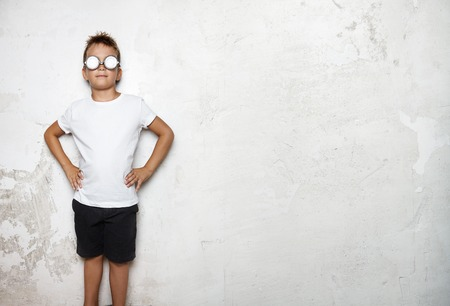curiosity: Boy wearing white tshirt, shorts and glasses, stands on a wall background and smiling Stock Photo