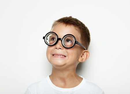 funny boy: Portrait of a little boy with glasses surprised by what he saw in the sky