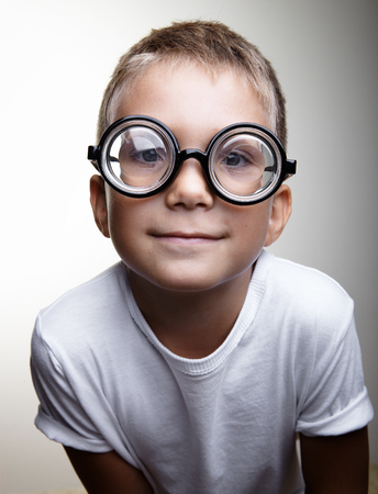 funny people: Cute little boy with glasses and white tshirt smiling on the white wall background
