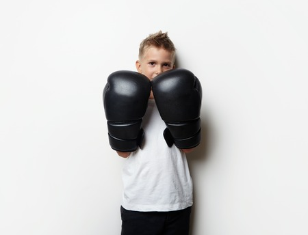boxing boy: Little boy standing in boxing gloves on theblank wall background and he ready to fight Stock Photo