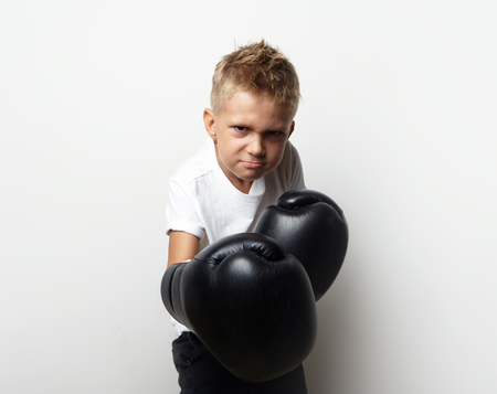 boxing boy: Little boy standing in boxing gloves on the blank wall background and he ready to fight