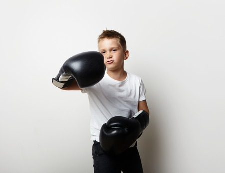 jab: Little boxer standing in boxing gloves on the blank wall background and shows his jab Stock Photo