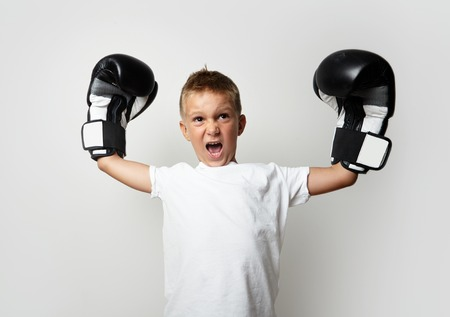 Young boy with boxing gloves celebrating his victory on the blank wall background