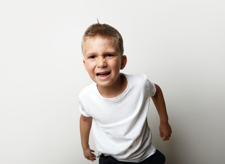 disturbance: Portrait of a little boy in white t-shirt. He is very upset and ready for action. Blank wall on the background