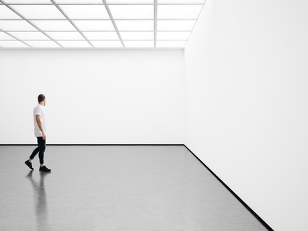 A man walks on the exhibition hall and examines the gallery of the exhibition