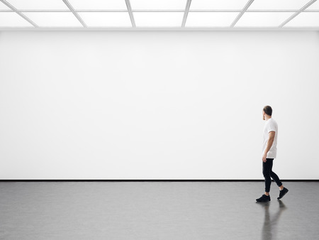 mock up: A man walks on the exhibition hall and examines the gallery of the exhibition