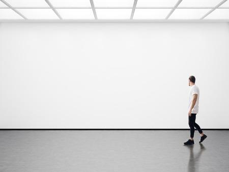 bonhomme blanc: Un homme marche sur le hall d'exposition et examine la galerie de l'exposition