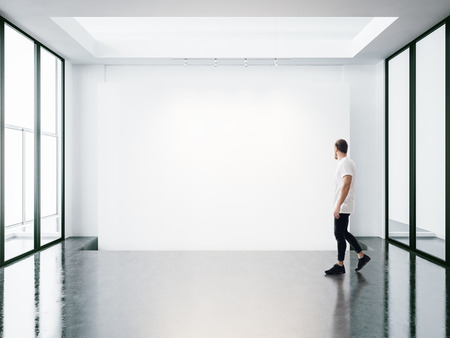 A man walks on the exhibition hall and examines the gallery of the exhibition 版權商用圖片 - 46775580