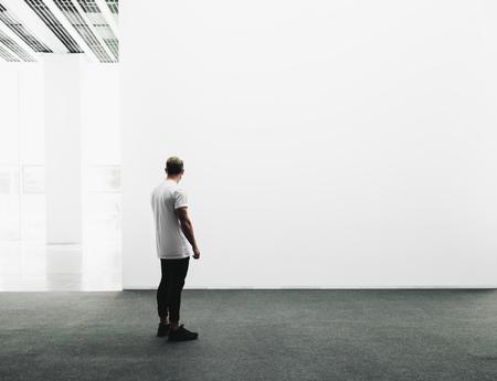 Un homme marche sur le hall d'exposition et examine la galerie de l'exposition Banque d'images - 46775588