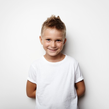 hands behind back: Little boy holds his hands behind his back and smiling on the blank wall background Stock Photo