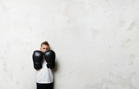 boy boxing: Little boy standing in boxing gloves on the concrete wall background and he ready to fight