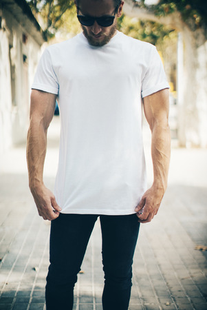 Portrait of a bearded guy wearing blank t-shirt, blue jeans, white tshirt and black sunglasses