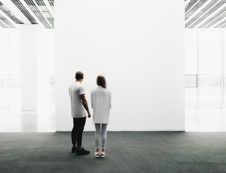 A man and woman walking through on the exhibition hall and examines the gallery of the exhibition