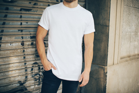 Portrait of a bearded man wearing blank t-shirt, blue jeans and standing on the street next to the garage Stock Photo