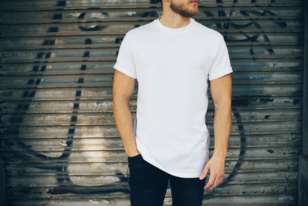 to white: Portrait of a bearded man wearing blank t-shirt, blue jeans and standing on the street next to the garage Stock Photo