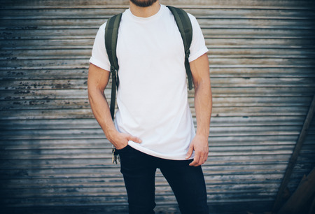 tshirts: Portrait of a bearded guy wearing blank t-shirt, blue jeans and green backpack Stock Photo