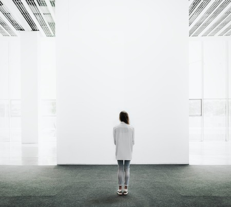 Young woman walking through on the exhibition hall and examines the gallery