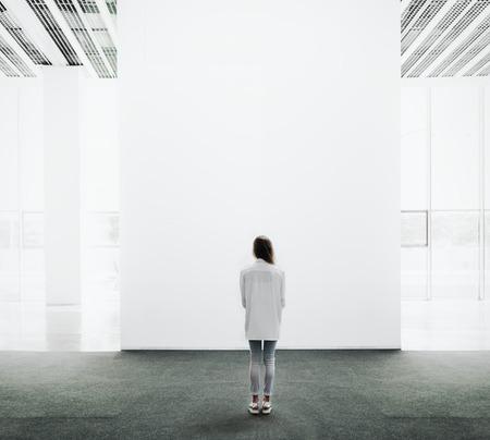 cuadrado: Mujer joven que recorre a trav�s de la sala de exposiciones y examina la galer�a Foto de archivo