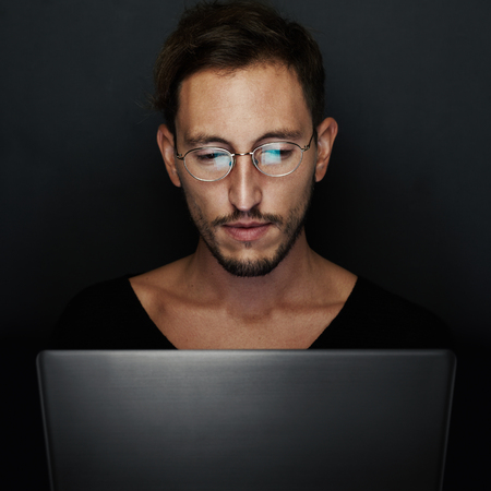 laptop computer: Portrait of handsome young man wearing glasses and working on the laptop. Black background Stock Photo