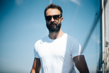 looking good: Portrait of young bearded man standing on a yacht and looking good Stock Photo