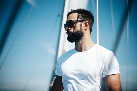 sunglasses: Portrait of young bearded man standing on a yacht and looking at the horizon