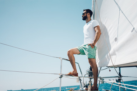 yacht people: Low angle view of young bearded man standing on the nose yacht. Horizontal mockup