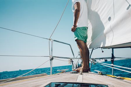 sailing: Low angle view of young man standing on the nose yacht. Horizontal mockup