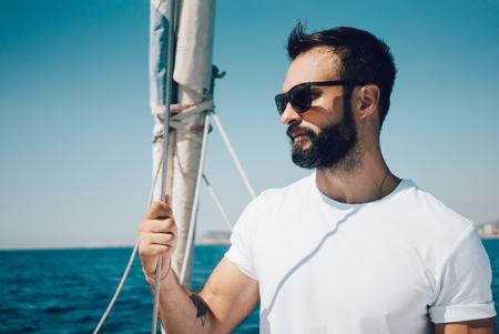 voilier ancien: Portrait de jeune homme barbu debout sur un yacht et regardant l'horizon