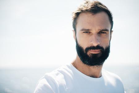 잘 생긴 수염 난된 남자 wuring 흰색 tshirt의 초상화. 흐린 배경 스톡 콘텐츠