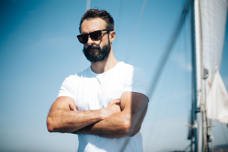 man looking: Portrait of young bearded man standing on a yacht and thinking about his life