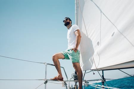 voilier ancien: Faible angle de vue d'un jeune homme barbu debout sur le yacht. Horizontal mockup