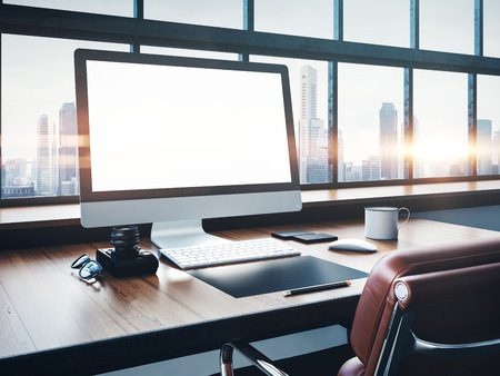 Photo of generic design computer screen and workspace in loft with panoramic windows and city on the background