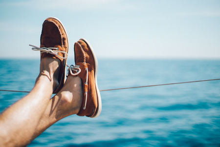Photo of man legs on the yacht and wearing boat shoes. Horizontal mockup