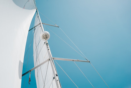 sail: Big white sail of a sailing boat against the sky.