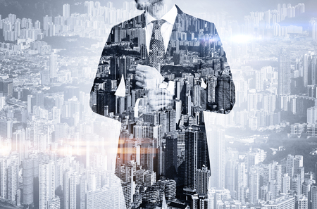 Double exposure of young  businessman touching his watch and the skyscraper on the background